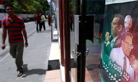 A man walks past a poster which shows former Maldivian presidents Mohamed Nasheed, Abdul Gayoom, and the newly appointed president Mohamed Waheed Hassan Manik