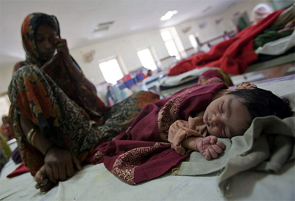 A woman who recently gave birth sits on a bed along with her new born baby
