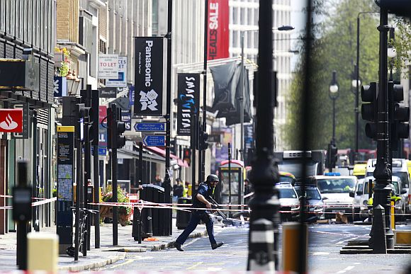 An armed police officer runs in Tottenham Court Road in central London during the hostage crisis