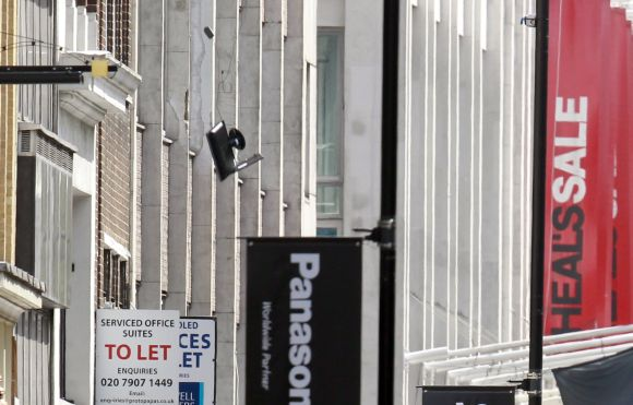 Computer equipment falls from an office window in Tottenham Court Road in central London on Friday