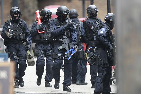 Armed police officers walk in Tottenham Court Road in central London on Friday during a hostage crisis