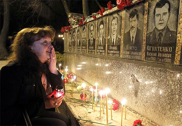 A woman cries in front of a memorial dedicated to firefighters and workers who died after the Chernobyl nuclear disaster during a night service near the Chernobyl plant