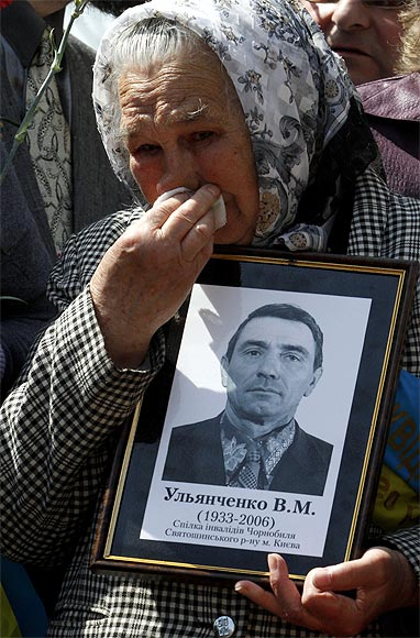 A woman holds a portrait of a victim of the Chernobyl nuclear disaster during a ceremony in Kiev