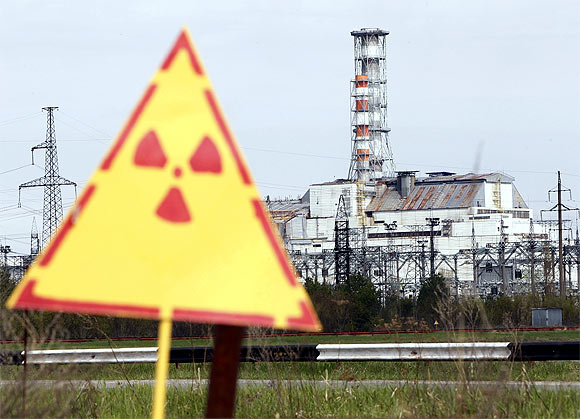 A hazard sign indicating radiation is seen in front of a containment shelter for the damaged fourth reactor at the Chernobyl nuclear power plant
