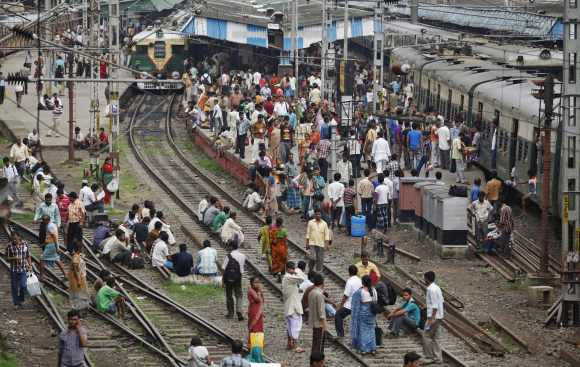 Passengers crowd at a railway station as they sit on tracks while waiting for the electricity to be restored in Kolkata on Wednesday