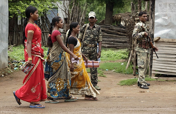 Government-backed militias stand guard as women walk past in Awapalli village, in Chhattisgarh