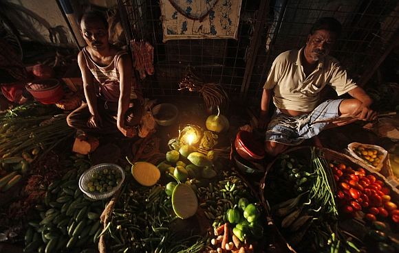 Vegetable vendors wait for customers at their stall during a power-cut in Kolkata
