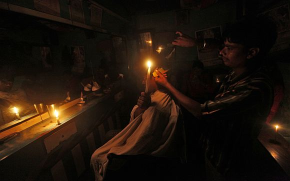 A customer holds a candle as he gets his haircut at a barber's shop during a power-cut in Kolkata