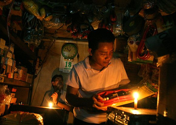 Merchants work with the help of candles at a market in Jakarta's China town August 18, 2005
