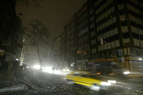 Motorists head home during a snow storm in a busy shopping district