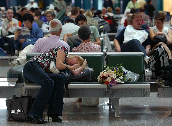 A woman sleeps on her luggage as she waits at Rome's Fiumicino airport September 28, 2003
