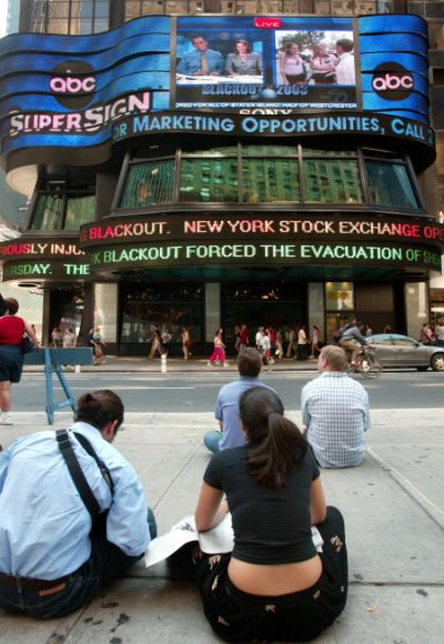 A group of people watch headlines on a board in New York's Times Square August 15, 2003, after the biggest power outage in North American history blacked out New York and other major US and Canadian cities