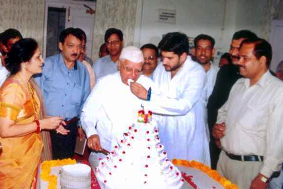 Rohit Shekhar feeds ND Tiwari a piece of cake on the latter's birthday.