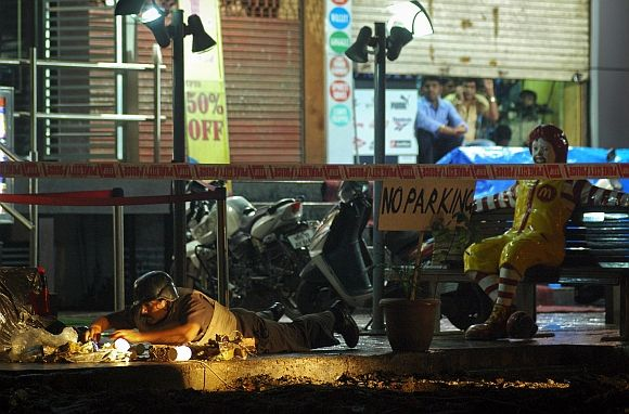A policeman inspects the site of an explosion near McDonalds restaurant in Pune on Wednesday