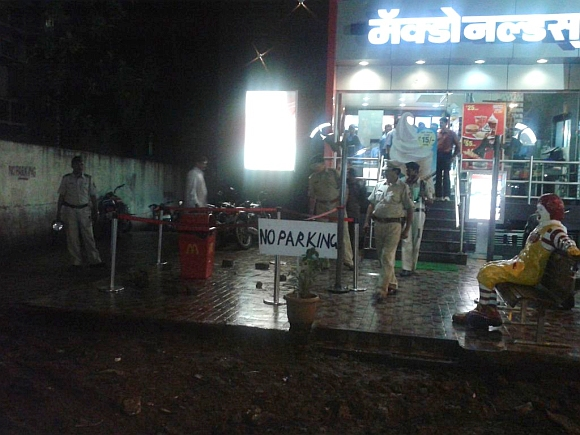 A policeman inspects the site of an explosion near McDonalds restaurant in Pune