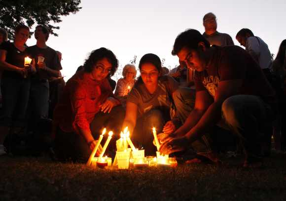 People light candles during a vigil at Cathedral Square to honor victims of Oak Creek in downtown Milwaukee after the gurudwara shooting