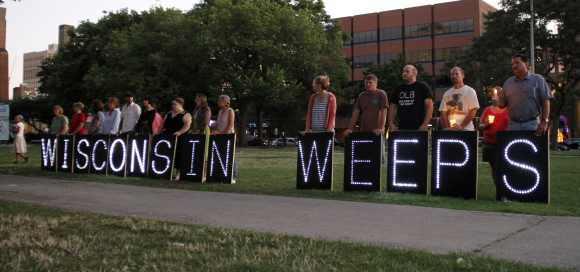 People stand holding a sign expressing their feelings during a vigil at Cathedral Square to honor victims of Oak Creek in downtown Milwaukee, Wisconsin