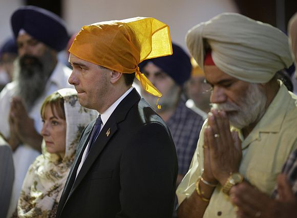 Wisconsin Governor Scott Walker attends a prayer service at the Sikh Temple in Brookfield, Wisconsin