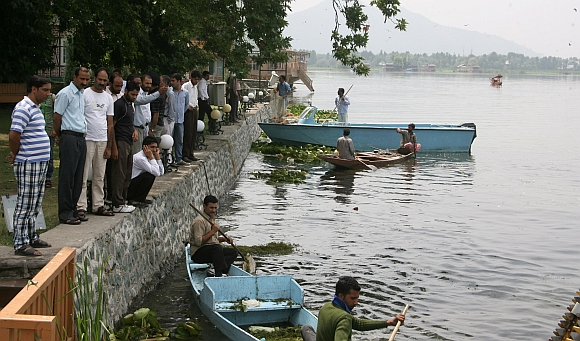 Government labourers clear dead fish as people look on