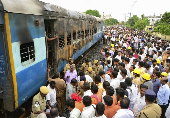 Onlookers stand next to a burnt carriage of the Tamil Nadu Express at Nellore station on July 30. 30 people lost their lives in the mishap