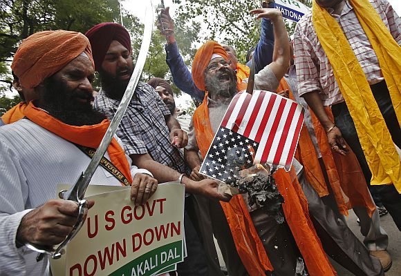 Activists from National Akali Dal, a regional Sikh political party, hold swords and shout slogans during a protest against Sunday's shooting at a Sikh temple in Wisconsin, US, in New Delhi