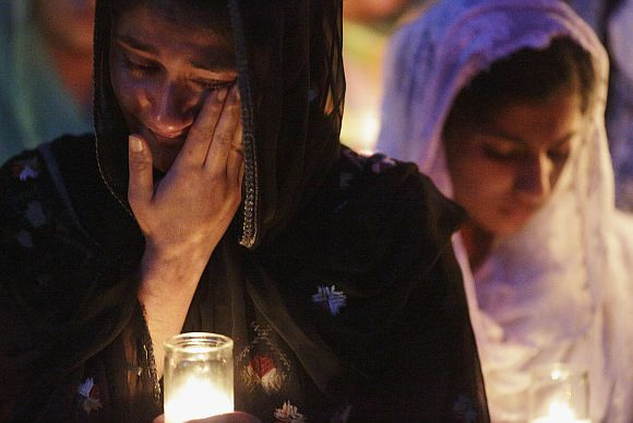 Mourners cry during a candlelight vigil at the Sikh temple in Brookfield, Wisconsin