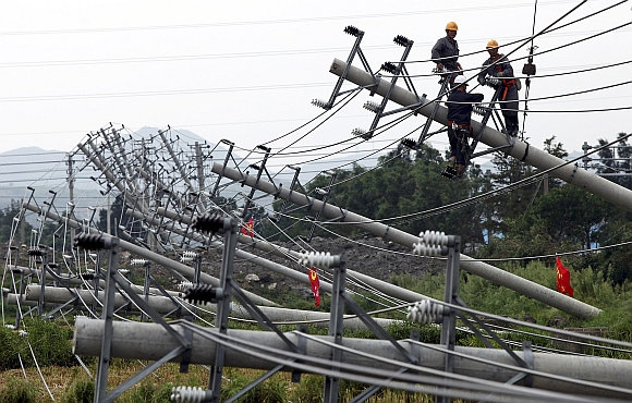 Labourers work to reconnect an electric circuit after pylons were turned over by Typhoon Haikui in Wenling, Zhejiang province