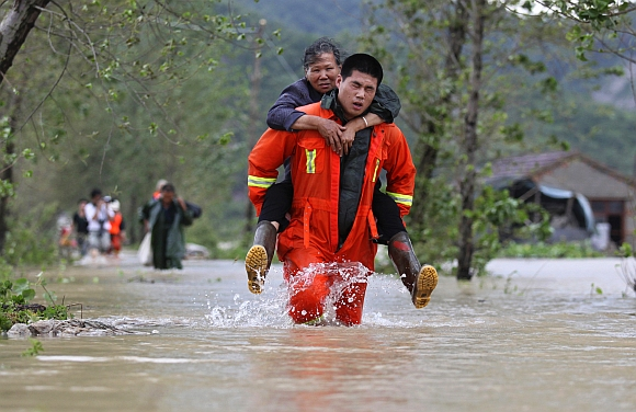 A rescuer carries a woman to a safer area in Taizhou, Zhejiang province