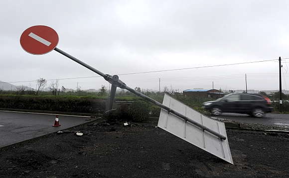 A car drives past a damaged traffic sign as Typhoon Haikui hits Hepu township, Zhejiang province