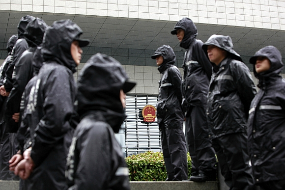 Police officers stand outside the Hefei Intermediate People's Court, where Gu Kailai's trial was held