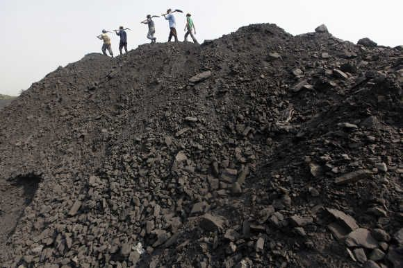 Workers walk on a heap of coal at a stockyard of an underground coal mine in Odisha