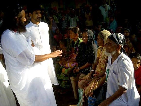 Sri Sri Ravi Shankar distributing relief material at the Basugaon Higher Secondary School relief camp
