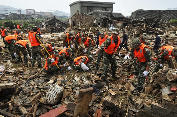 Paramilitary police officers search for victims amongst debris of destroyed houses after a flood caused by a dam breach in Daishan county, Zhejiang province