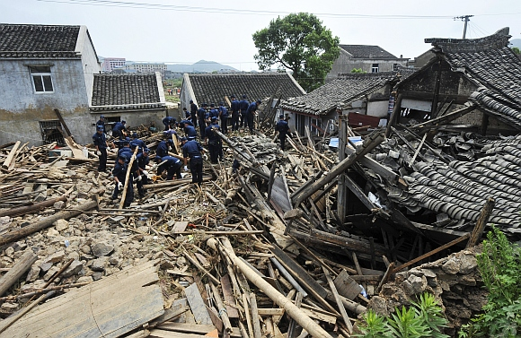 Chinese navy soldiers search for victims amongst debris of destroyed houses after a flood caused by a dam breach in Daishan county, Zhejiang province