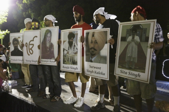 Sikhs hold up placards with photos of six mass shooting victims after a candlelight vigil in Oak Creek, Wisconsin