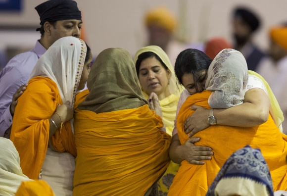 Family members and mourners gather during a wake and visitation service for victims of last Sunday's attack at a Sikh temple