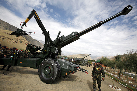 A soldier walks past a Bofors artillery gun