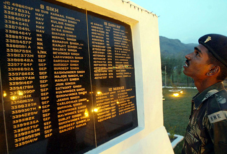 A soldier looks at the names of fallen colleagues at a war memorial during Vijay Diwas