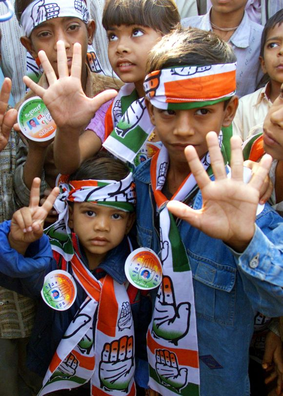 Children display campaign material of the Congress party near a polling booth in Gujarat