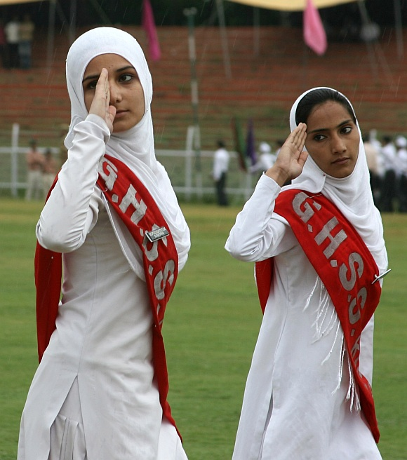 College girls salute during a parade after unfurling of the Tricolour