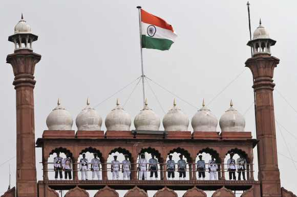 Buglers from the armed forces stand on the balcony of the historic Red Fort as the national flag flutters during the full-dress rehearsal for Independence Day celebrations