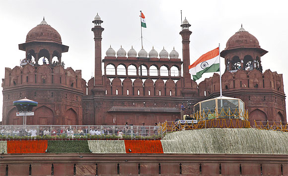 Dr Singh addresses the nation from a bullet-proof enclosure as national flags flutter at the historic Red Fort during Independence Day celebrations in Delhi