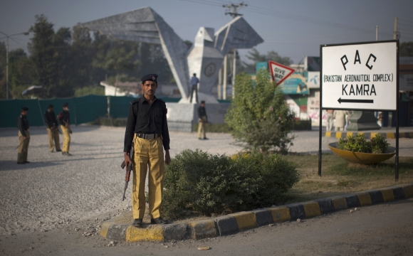 Policemen stand guard near the site of a suicide bomb attack at the entrance of the Pakistan Aeronautical Complex in Kamra