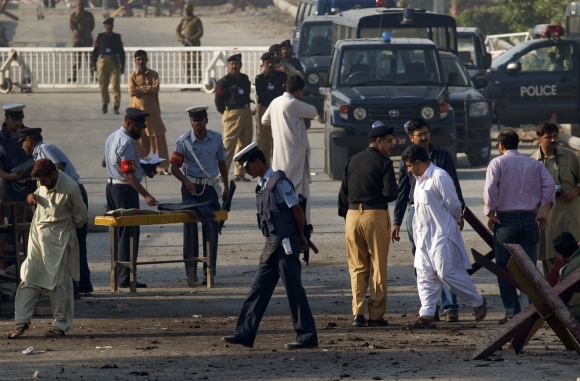 Security forces survey the site of a suicide bomb attack at the entrance of the Pakistan Aeronautical Complex in Kamra