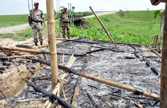Army men monitor the scene of violence in Assam