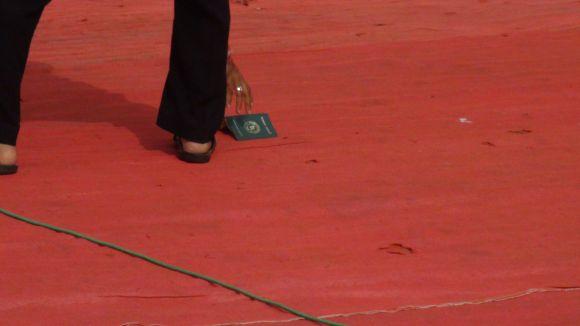 An MNS supporter picks up a Bangladeshi passport flung by Raj Thackeray while addressing a gathering at Azad Maidan