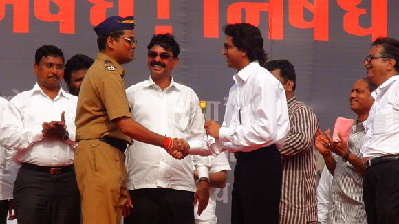 Pramod Shantaram Tawde, a Mumbai Police constable presents a rose to Raj Thackeray during MNS' rally at Azad Maidan on Tuesday