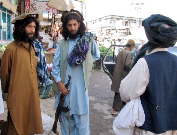 Pakistani Taliban militants stand guard in a busy market in Miranshah, the main town in North Waziristan region