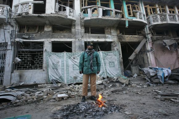A policeman stands in front of a damaged building which was hit by a bomb attack in Quetta in February, 2012.