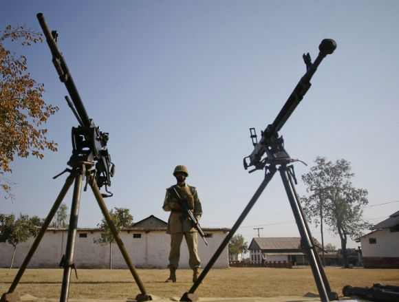 A Pakistan soldier stands guard near seized anti-aircraft guns, showcased to the media, at a military compound in Bara, Khyber Agency